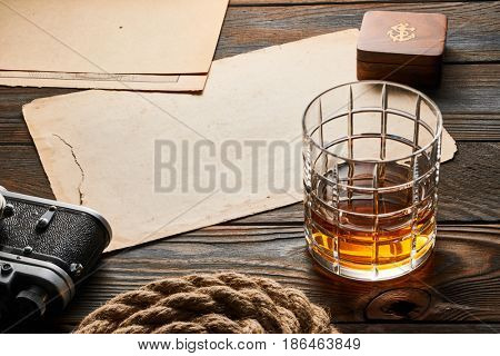 Glass of whiskey and vintage old 35mm rangefinder camera on wooden background with antique XIX century map