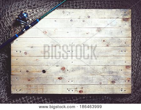 Top view of fishing nets and spinning rod on the wooden background.
