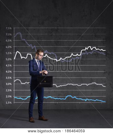 Businessman with briefcase standing on a diagram background. Business, finance, investment concept.