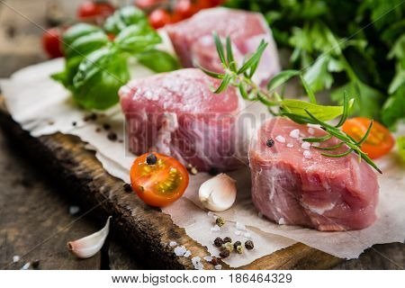 Raw filet mignon meat cuts with spice and herbs, wood background