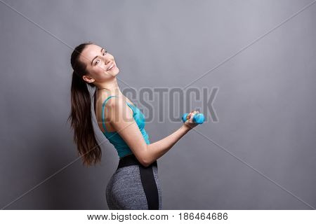 Fitness model woman with dumbbells at studio background. Young girl in fitwear at gray