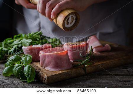 Preparing filet mignon - hands seasoning the steak, wood background