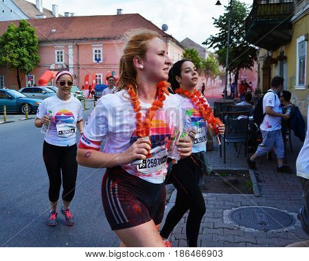 CLUJ-NAPOCA ROMANIA - May 14 2017: Beautiful young girls splashed with colored powder run on the street after passing the red powder color zone