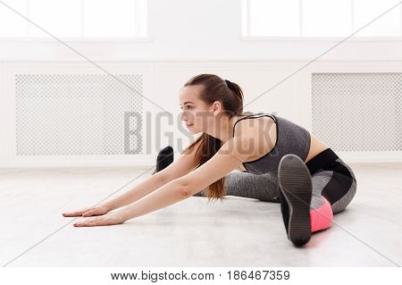 Woman yoga leg stretching at home. Young slim girl makes exercise