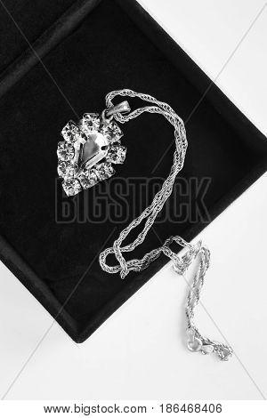 Vintage diamond pendant on silver chain in jewel box closeup