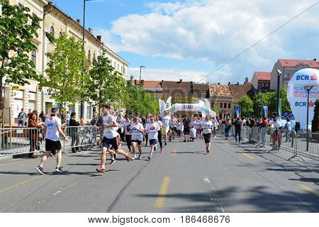 CLUJ-NAPOCA ROMANIA - May 14 2017: Color Run participants of all ages and genders wearing colorful t-shirts and headbands take off from the starting line as the race begins.