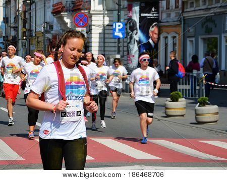 CLUJ-NAPOCA ROMANIA - May 14 2017: Beautiful young girl runs on the street at the Color Run followed by people of all ages