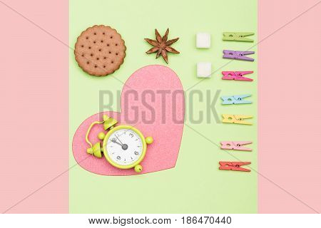 Heart symbol on a light green and pink background with alarm clock on it next to anise flower cookie sugar cubes and clothespins. Valentines day concept