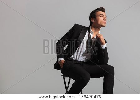 young man in tuxedo and undone bowtie dreaming while sitting on chair in studio
