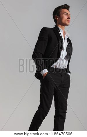 side view of a walking young man in tuxedo and undone bowtie dreaming away on grey background