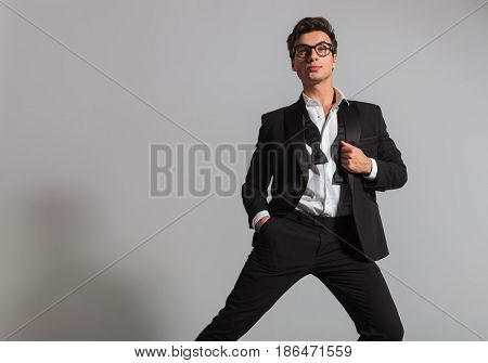 elegant man in tuxedo and undone bowtie leaning on one leg and looks up to something on grey studio background