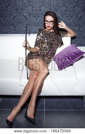 Sexy dominant woman holding whip sitting on sofa