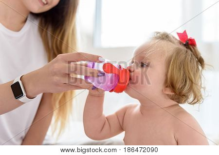 Enjoying motherhood. Happy young woman is giving small bottle of water to her little child. She is holding it near her mother and smiling
