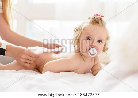 Lovely baby girl is lying on bed while her mother wearing nappy on her. Infant is looking at camera with interest and sucking a dummy. Portrait