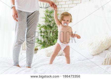 Concentrated baby girl is standing on bed and holding mother hand. She is sucking pacifier