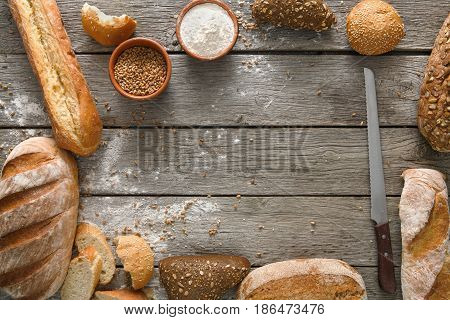 Fresh white bread frame background, top view with copy space. Homemade baguette loaves on rustic wood