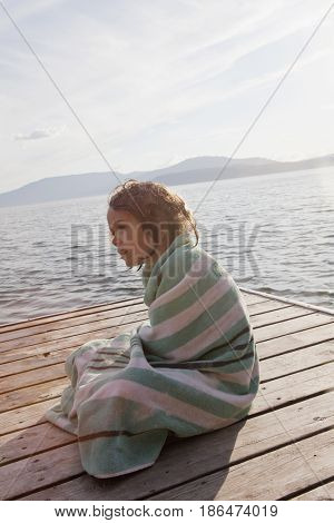 Caucasian girl sitting on pier wrapped in towel