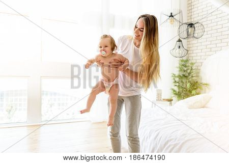 My happiness. Joyful young woman is holding her little daughter and laughing. She is standing in bedroom. Baby is keeping pacifier in mouth