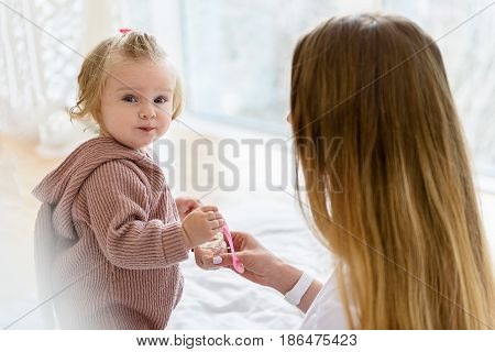 Portrait of happy little child enjoying food fusion. She is looking at camera with curiosity while her mother is sitting near her