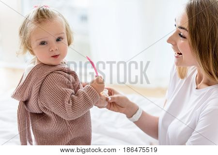 Interesting baby girl is eating tasty food fusion by herself. She is holding spoon. Her mom is giving jar to her and laughing