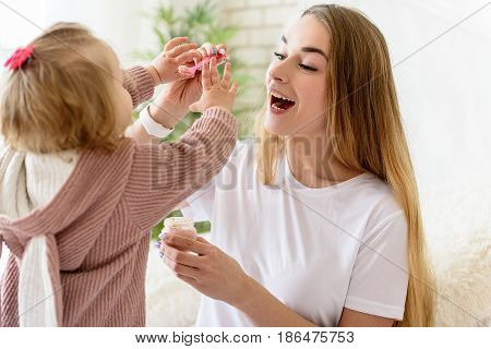 Joyful young woman is feeding her little child with healthy food fusion. She is stretching spoon forward and laughing