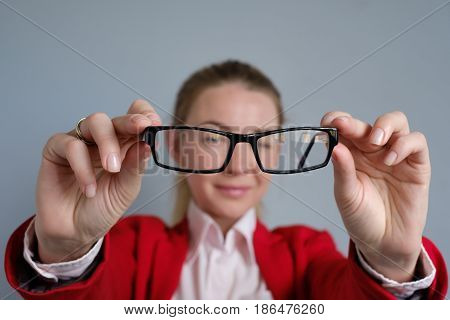 woman is holding glasses in her hands. Her eyes are tired of prolonged work.