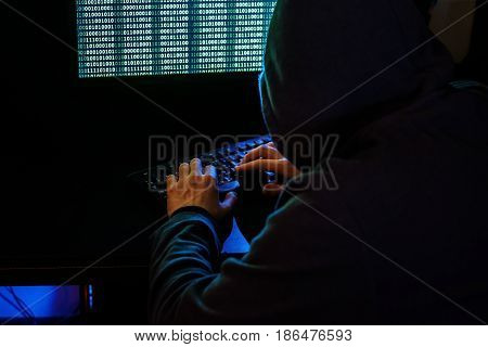 The Man In The Hood Checks The Malicious Code On The Keyboard. Cybercrime Through The Internet.