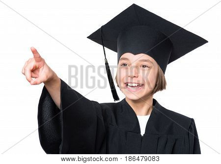 Portrait of a graduate little girl student in a black graduation gown with hat pointing and looking away - isolated on white background. Child back to school and educational concept.