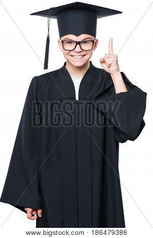 Portrait of a graduate teen boy student in a black graduation gown with hat has idea, pointing with finger up - isolated on white background. Child back to school and educational concept.