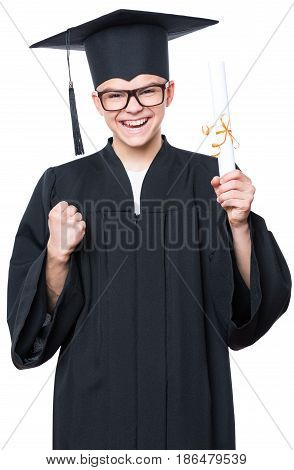 Portrait of a graduate teen boy student in a black graduation gown with hat, holding diploma - isolated on white background. Lucky cheerful schoolboy celebrating triumph.