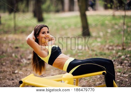 Woman Exercising With Exercise Equipment In The Public Park. Woman In A Sports Simulator Training On