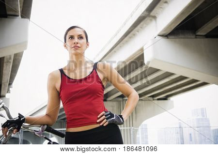 Hispanic woman standing in urban area with bicycle