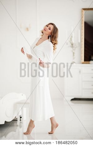 Portrait of sensuality beautiful woman in white dress standing on toes and undressing, holding strap in hand. Gorgeous girl with wavy hair after beauty salon posing in luxury interior.