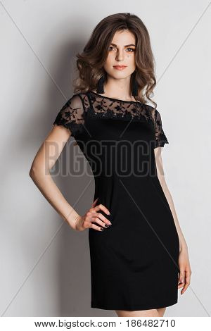 Beautiful young brunette with wavy short hair wearing in nightie black dress with element of lace posing at camera. Girl with slim sexy figure, pure skin and perfect make up holding hand on waist.