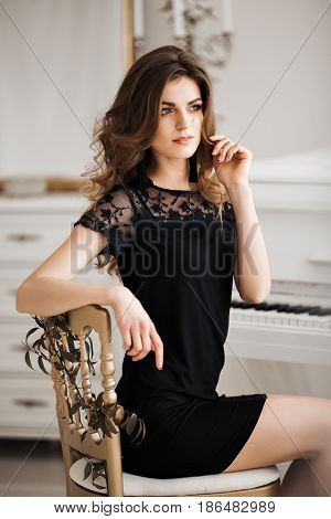 Beautiful woman with wavy hair and perfect make up leaning on chair, posing, looking away, touching face. Seductive brunette   sitting on chair with element of gold wearing in black nightie dress.