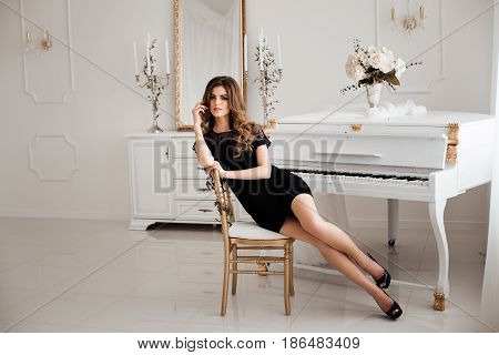 Seductive brunette woman with perfect figure, in black nightie dress leaning on chair and posing at camera. Beautiful girl with makeup and wavy haircut, long legs against piano at luxury interior.