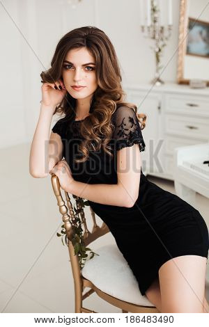 Sexy brunette woman wearing in black nightie dress with wavy hair and perfect make up leaning on chair and posing. Beautiful female sensuality touching face and looking at camera. Morning look.