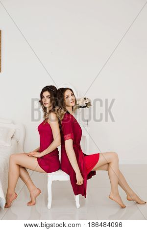 Couple of two seductive and beautiful girls in red nighties sitting in bed room and leaning back to back, posing at camera. Sexy girlfriends  with make up and wavy hairstyle in luxury interior.