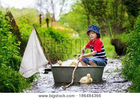 Cute Child, Boy, Playing With Boat And Ducks On A Little Rive