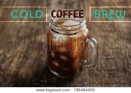 Glass jar of cold brewed coffee on wooden background