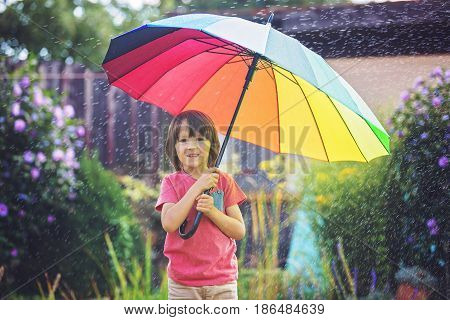 Cute Adorable Child, Boy, Playing With Colorful Umbrella Under Sprinkling Water