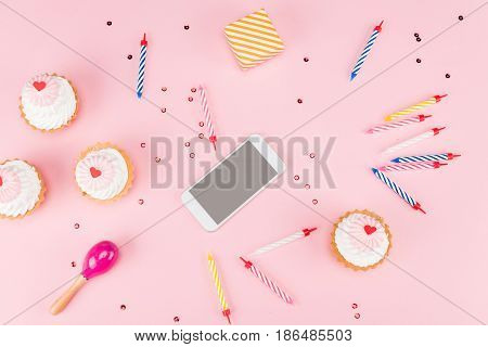 top view of cakes with candles and smartphone with beanbag mock-up birthday party