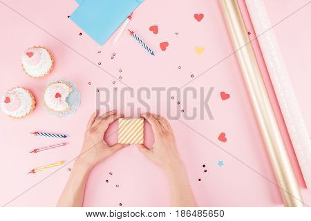 Partial Top View Of Hands Wrapping Gift Box And Delicious Cupcakes On Pink, Birthday Party Concept