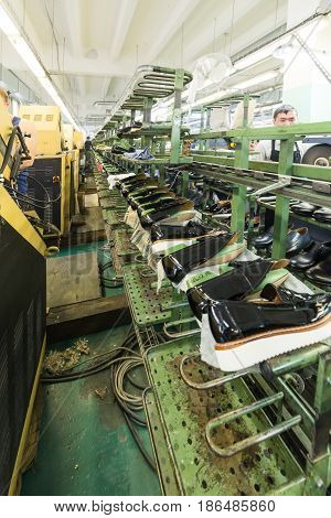 MOSCOW, RUSSIA - FEBRUARY 21, 2017: Moscow shoe factory JSC RALF RINGER. Black lacquer shoes on the conveyor of the shoe factory.