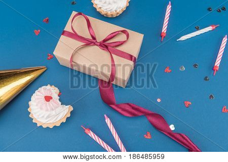 Side View Of Gift Box, Cakes And Candles Isolated On Blue, Birthday Party Concept