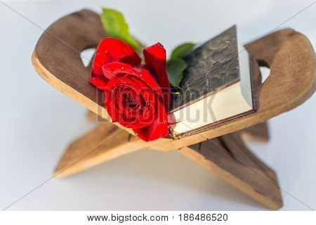 holy kuran and red flower on stand