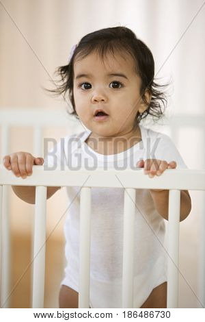 Hispanic baby girl standing in crib