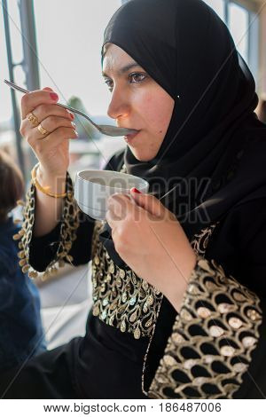 muslim woman eating soup from bowl