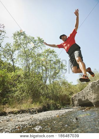Mixed race man jumping into stream