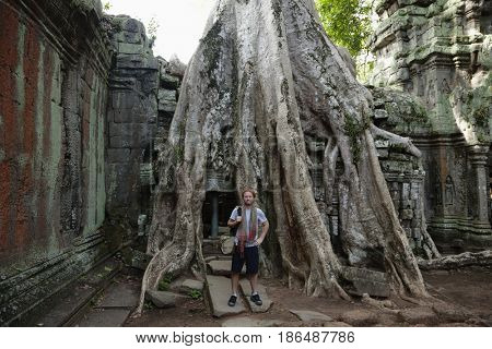 Caucasian man standing by large tree roots in ruins
